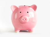 Cute pink piggy bank against white background