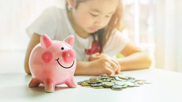 A cute pink piggy bank and pile of coins on table with background of asian little girl stock photo