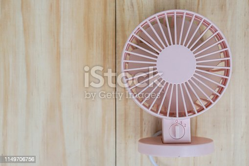 istock cute pink portable USB fan on wooden frame for cool temperature 1149706756