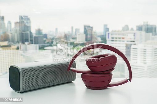 cute pink wireless headphone with bluetooth portable speaker on office desk for relaxation