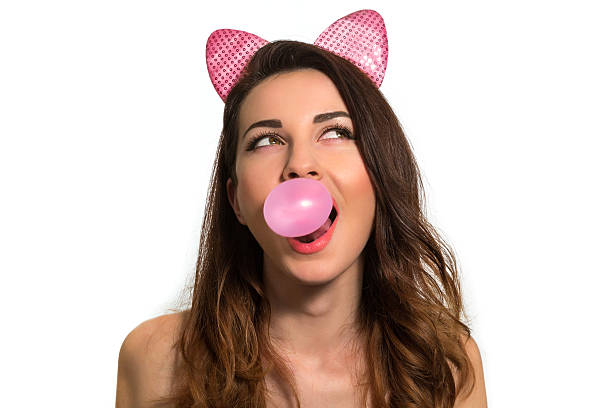 Cute playful girl blowing pink chewing bubble gum looking up stock photo