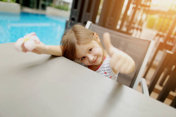 cute portrait of little kid girl showing thumbs up or like on swimming pool - mulher natureza flores e piscina imagens e fotografias de stock