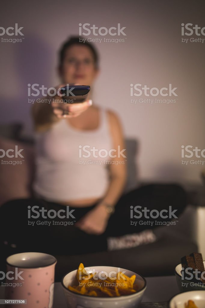 Cute pregnant woman switching channels on TV stock photo
