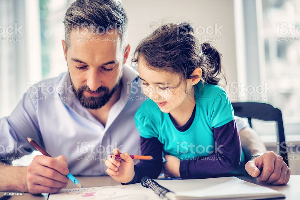 cute prescholar girl and father drawing together at home stock photo