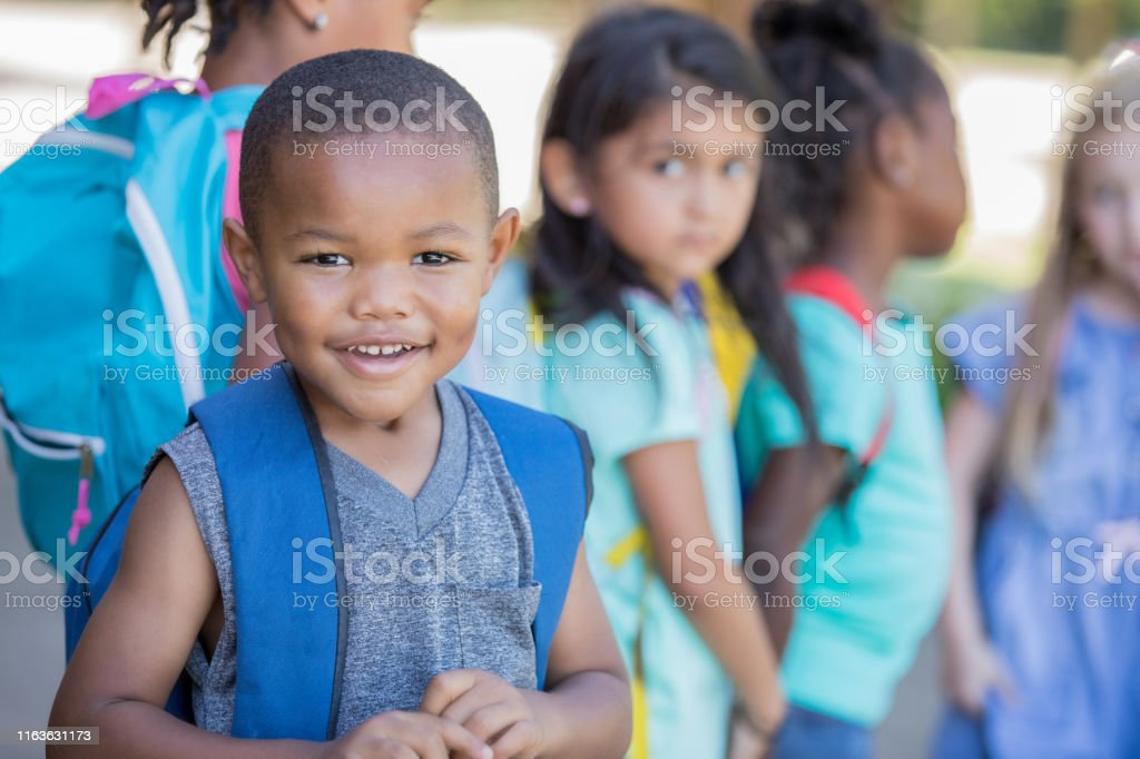 Cute preschool age little boy is wearing a backpack and standing...