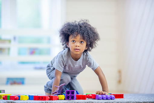 An adorable preschool boy of African descent is on the classroom floor playing with colourful blocks.