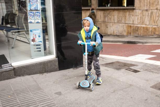 Niedliches Vorschulkind Junge mit dem Roller zur Schule in Barcelona, Spanien. – Foto