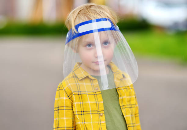 Cute preschooler child wearing face shield walking on street of city during coronavirus epidemic. Social distancing and face mask - security measures when exiting quarantine stock photo