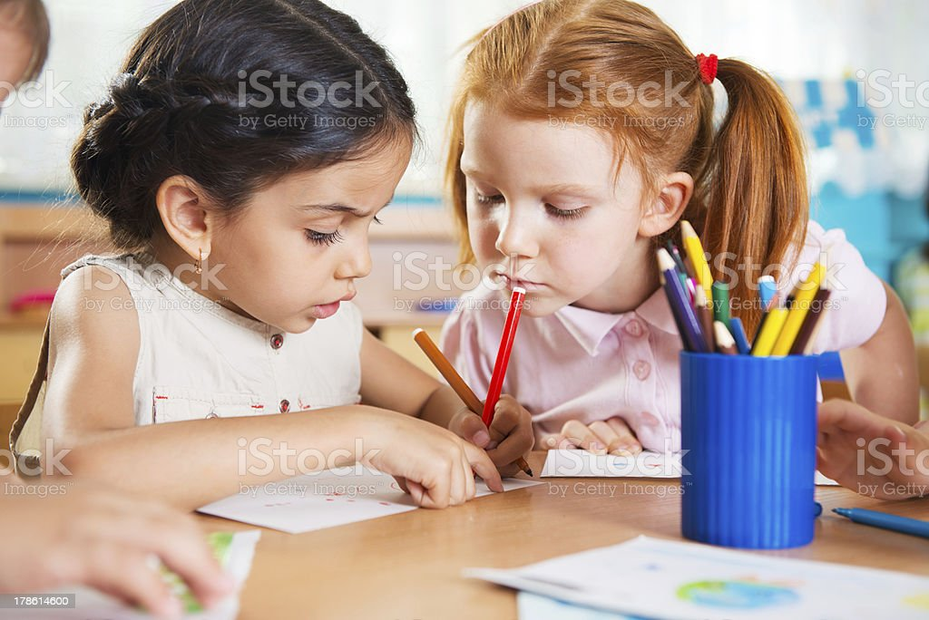 Cute preschoolers drawing with colorful pencils stock photo