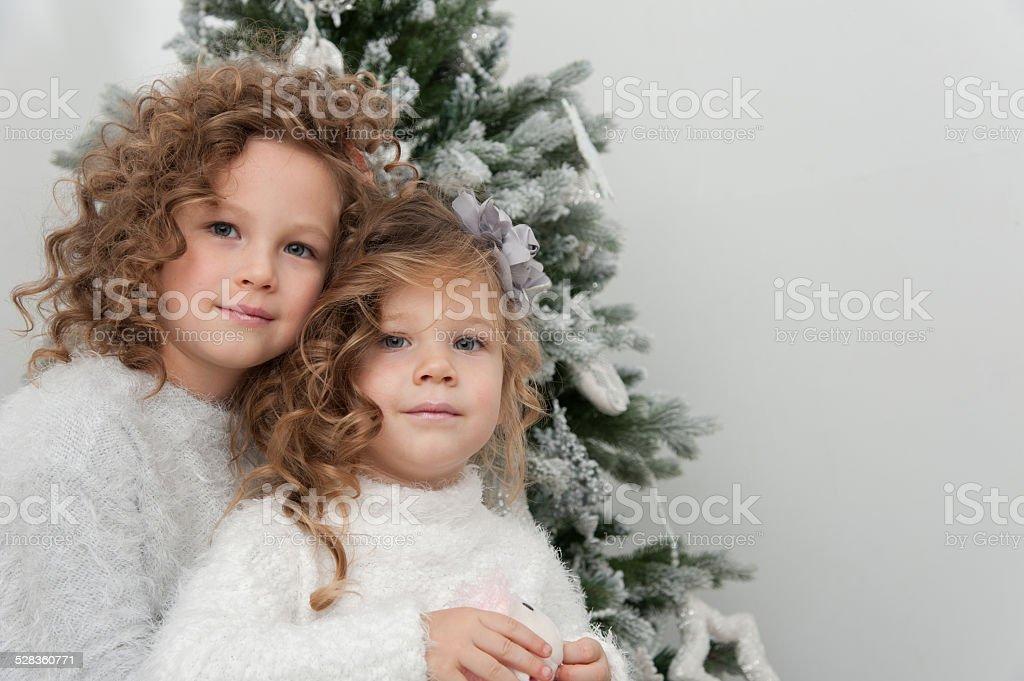 Cute pretty smiling girls near Christmas tree stock photo