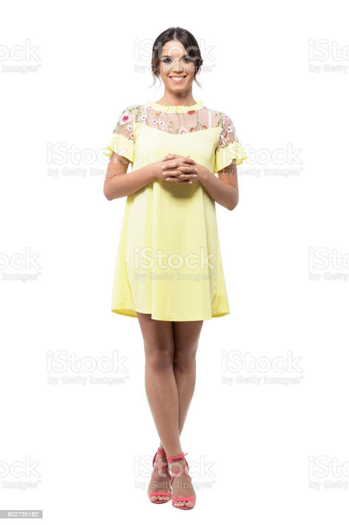 Linda mujer muy sonriente en vestido amarillo de pie con las manos Unidas mirando a cámara. - foto de stock