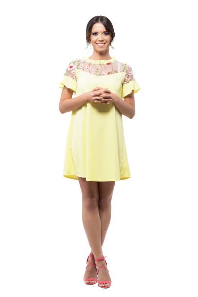 cute femme assez souriante dans une robe jaune debout avec les mains jointes, regardant la caméra. - présentateur photos et images de collection