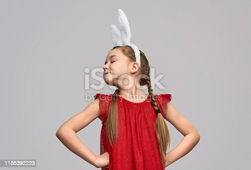 Charming arrogant girl in red dress and white ears of Easter bunny standing with hands on waist against gray background
