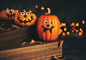 Cute pumpkin characters with handmade expressions and holiday lights