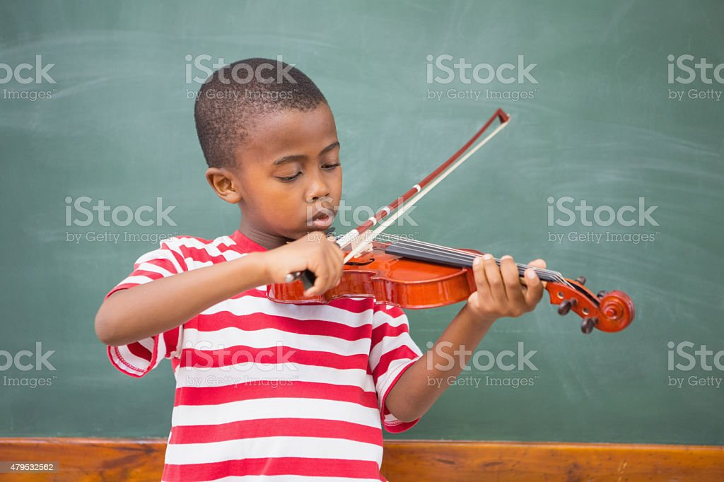 Cute pupil playing violin in classroom stock photo