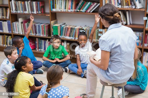 istock Cute pupils and teacher having class in library 819289862