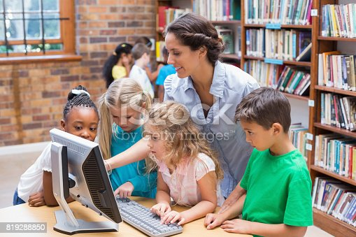 istock Cute pupils and teacher looking at computer in library 819288850