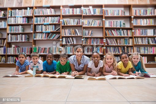 istock Cute pupils and teacher lying on floor in library 819290076