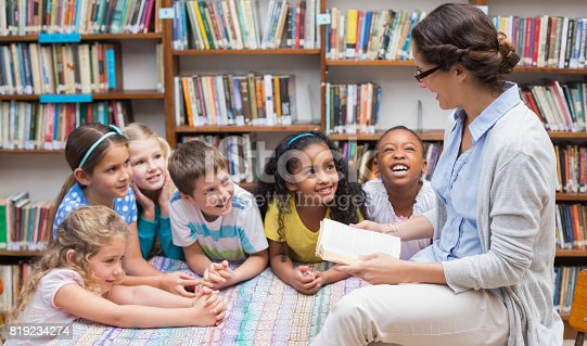 istock Cute pupils and teacher reading in library 819234274
