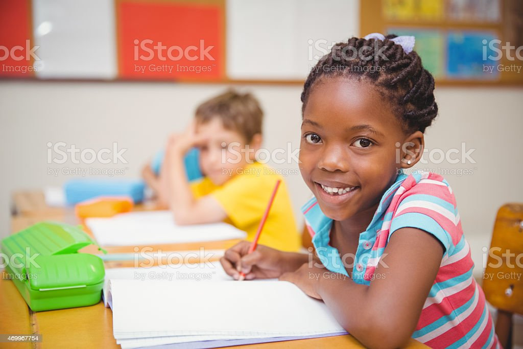 Cute pupils drawing at their desks stock photo