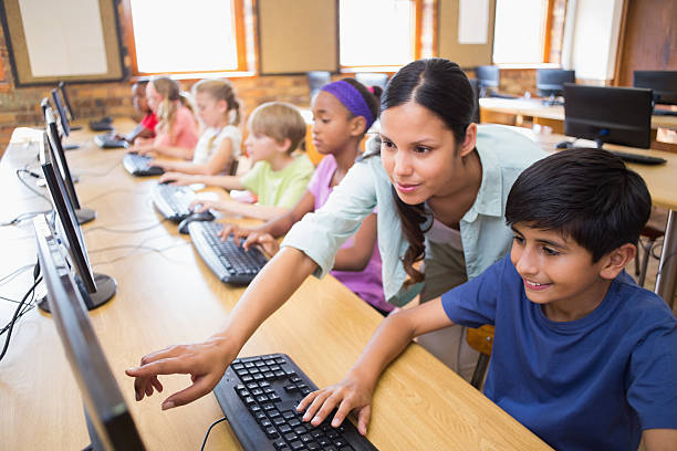 cute pupils in computer class with teacher - elementary age stock photos and pictures