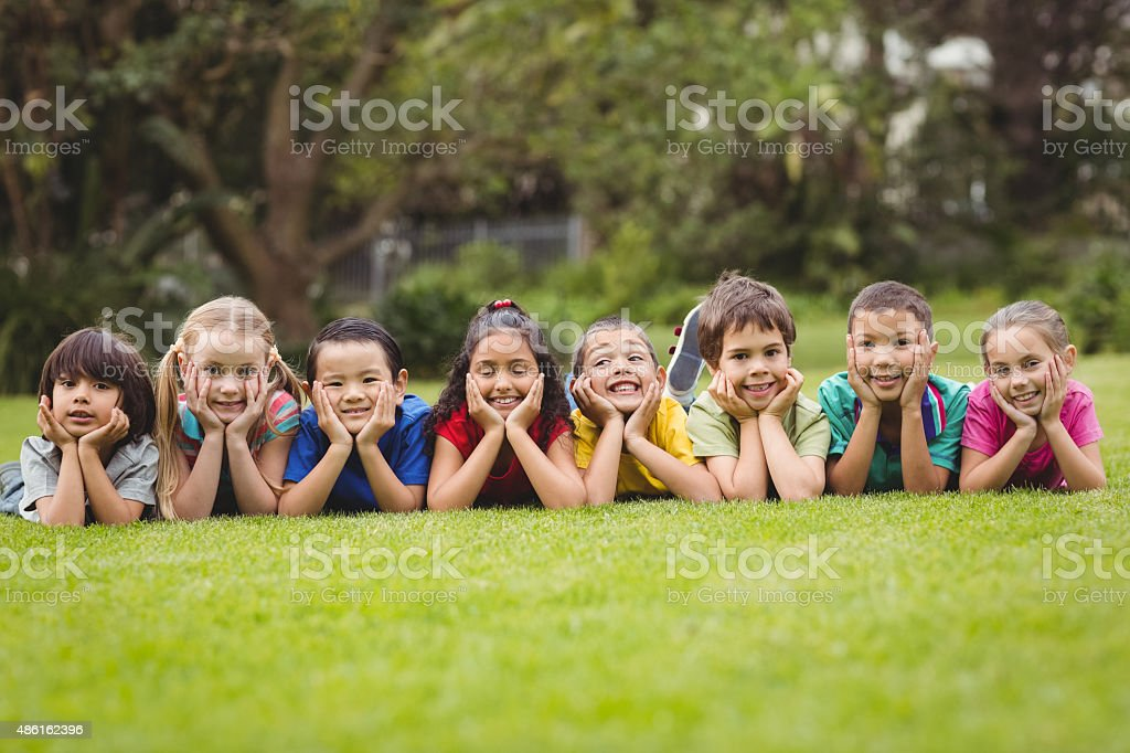 Cute pupils lying on the grass outside stock photo