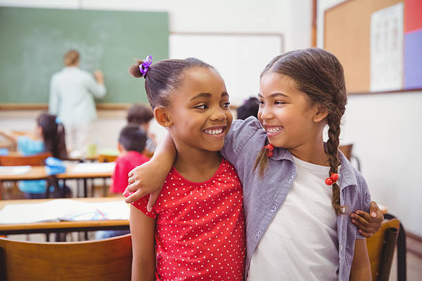 Cute pupils smiling at camera in classroom stock photo