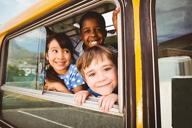 élèves mignons souriant à la caméra dans l'autobus scolaire - bus scolaires photos et images de collection