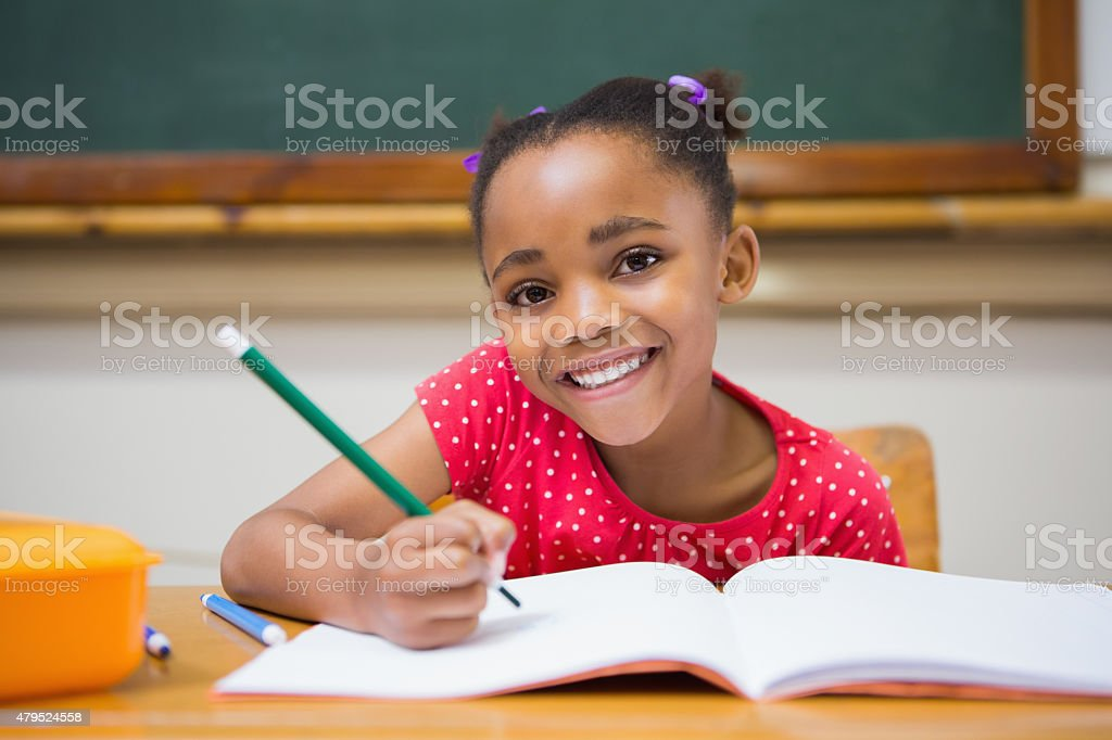 Cute pupils writing at desk in classroom stock photo