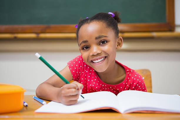 cute pupils writing at desk in classroom - 6 7 år bildbanksfoton och bilder