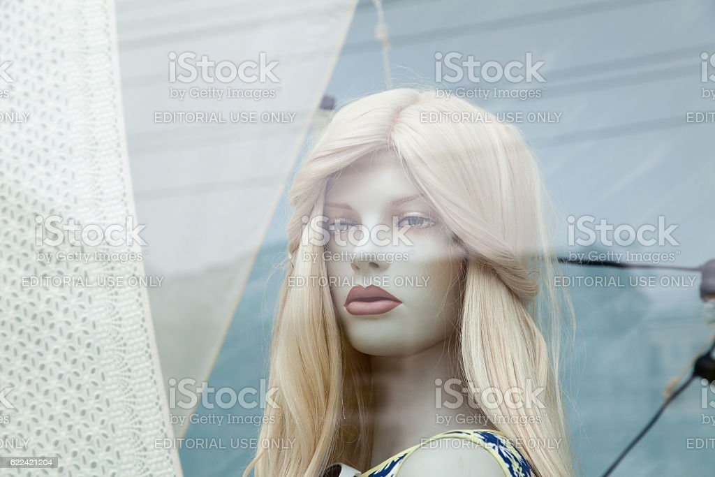 Cute realistic female mannequin face close-up in a shop window stock photo