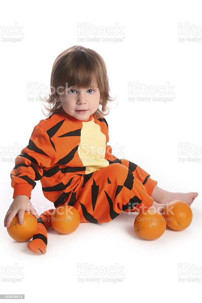 Cute red haired boy in tiger costume with oranges royalty-free stock photo