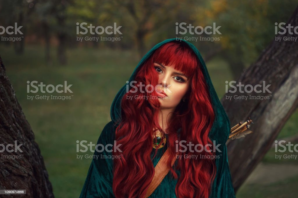 Cute Redhaired Girl Looks Into The Camera With Brown Eyes Wearing An Emerald Raincoat With A Hood On Her Head Has A Leather Quiver For Arrows And An Expensive Shiny Look On