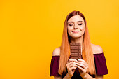 istock Cute red-haired young woman with pleasure and dreaminess holds a chocolate in her hands isolated on yellow background with copy space for text 1040986444