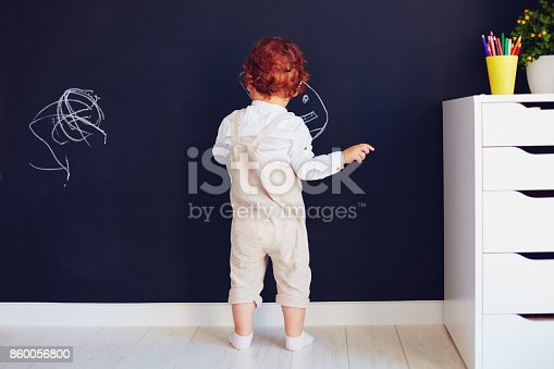istock cute redhead baby boy drawing on the chalk wall at home 860056800