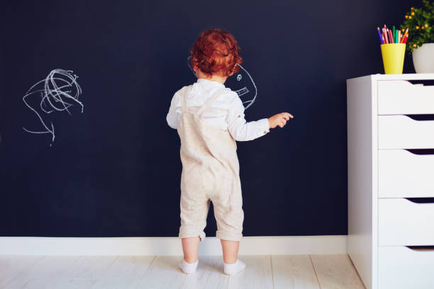 cute redhead baby boy drawing on the chalk wall at home stock photo