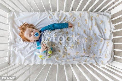 istock Cute Redhead Baby Boy Sleeping in the Crib 915503294