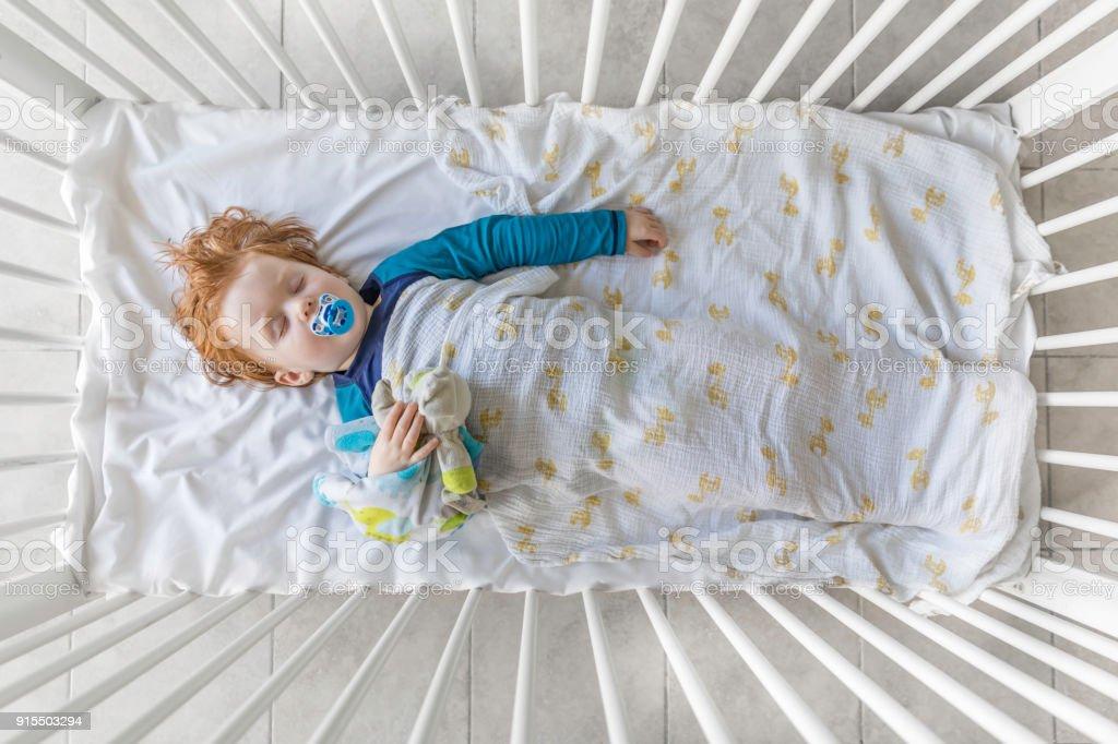 Niedliche Rothaarige Babyjungen schlafen in der Krippe – Foto