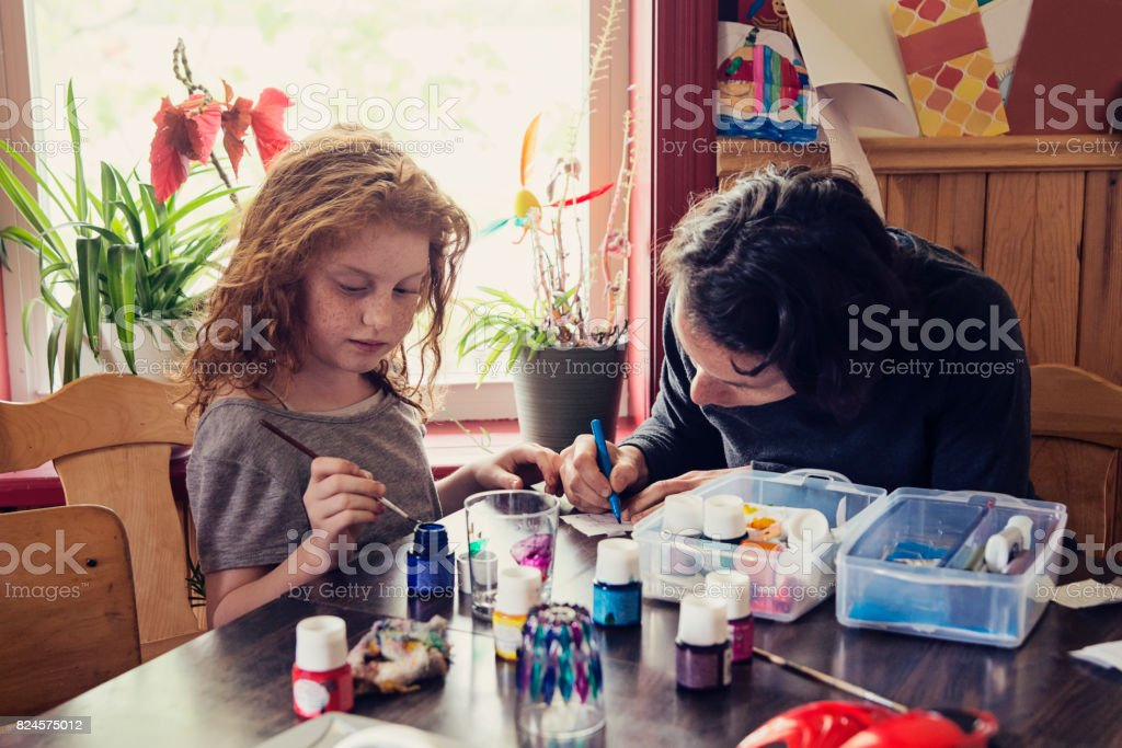 Cute redhead girl and aunt doing craft project at home. stock photo