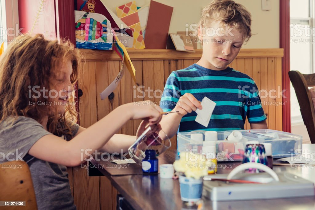 Cute redhead girl and cousin doing craft project at home. stock photo