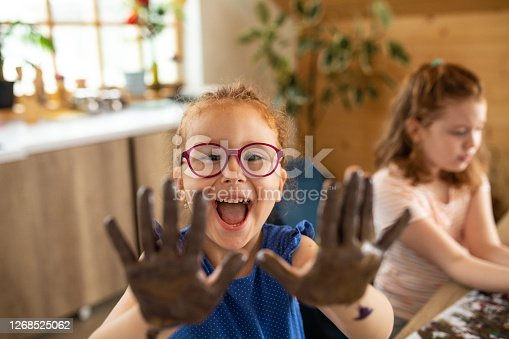 Cute redhead, cross-eyed girl showing her hands while finger painting with her friend at home