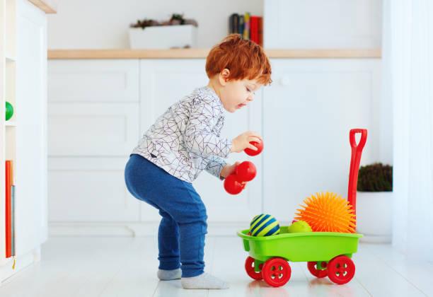 niedliche rothaarige kleinkind baby sammeln von verschiedenen kugeln in spielzeug schubkarre - spielesammlung stock-fotos und bilder