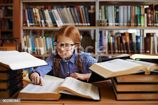 Smart girl surrounded with stacks of books reading dictionary