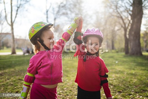 Beautiful young children enjoying the day at a park on rollerblades.