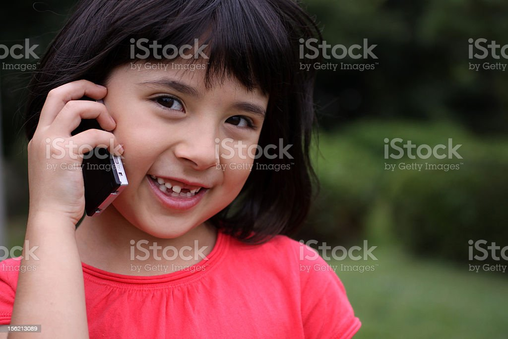 Cute Russian-Japanese talking and smiling outside on the phone stock photo