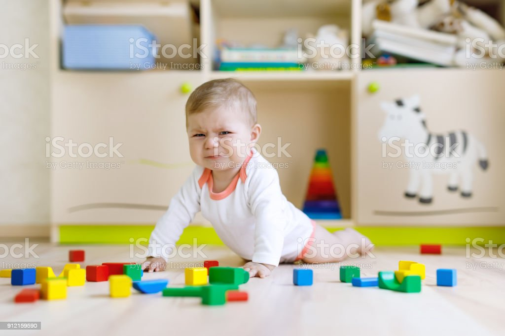 Cute Sad Crying Baby Playing With Colorful Wooden Blocks Toys Stock