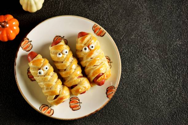 "Cute sausages in puff pastry  ""Mummy"" with ketchup and mustard  for the Halloween party. Children's food. stock photo"