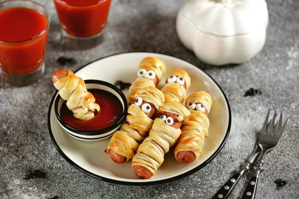 "Cute sausages in the dough ""Mummy"" with ketchup and spiders for the Halloween party. Children's food. stock photo"