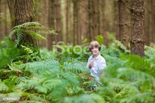 istock Cute school boy playing in a beautiful pine forest 478356517