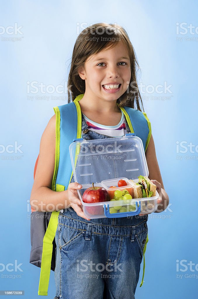 Cute school girl shows her healthy lunch box royalty-free stock photo